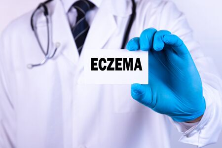 Doctor holding a card with text Eczema medical concept