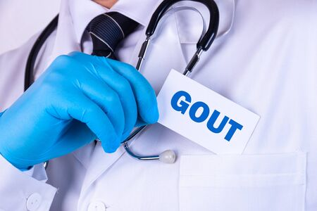 Doctor holding a card with text Gout medical concept Banco de Imagens