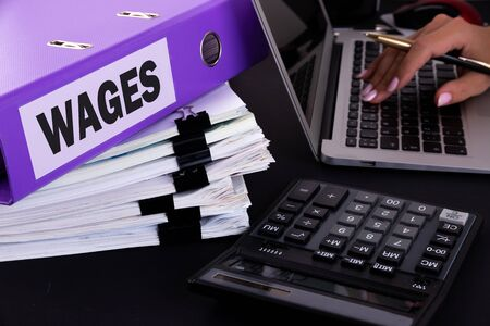 A business woman is surrounded by large bundles of documents. Above is a purple folder with the words WAGES