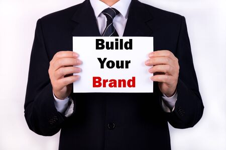 Businessman holding a card with text Build Your Brand