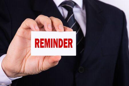 Businessman holding a card with text Reminder Standard-Bild