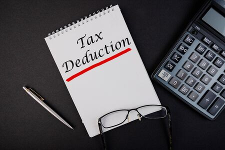 Tax deductions notepad writing concept on dark background with pen and calculator.