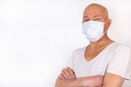A sick man in a medical mask stands on a white background. The concept of protection against viral infection.