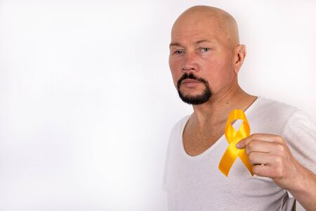 A man holds a yellow ribbon on the background of his t-shirt. Medical bone tumor cancer awareness concept.