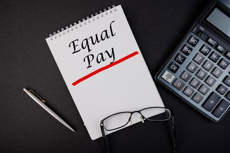 The inscription, the phrase Equal Pay is written in a notebook that lies on a dark table with a calculator and pen and glasses. Business concept.