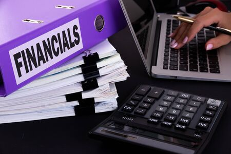Folder with the text FINANCIALS written on it lies on a dark office desk with a laptop, hand with pen, calculators and reports