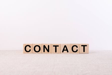 CONTACT word concept written on wooden cubes blocks lying on a light table and light background Banque d'images