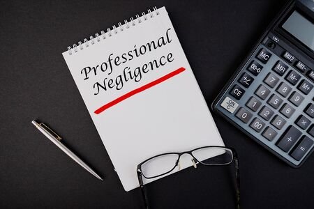 Text, the inscription, the phrase Professional Negligence is written in a notebook that lies on a dark table with a calculator and pen and glasses. Business concept.