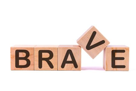Word BRAVE is made of wooden building blocks lying on the table and on a light background. Stock Photo