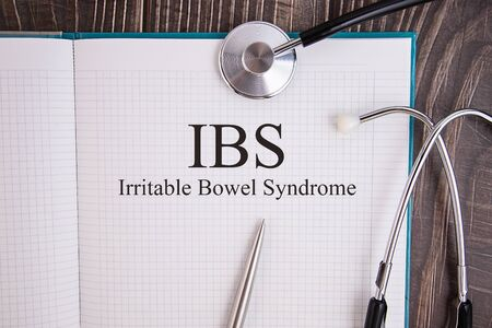Notebook page with IBS Irritable Bowel Syndrome text, on a table with a stethoscope and pen, medical concept.