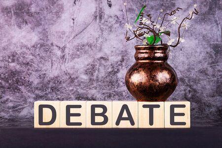 Word DEBATE made with wood building blocks on a gray back ground 版權商用圖片