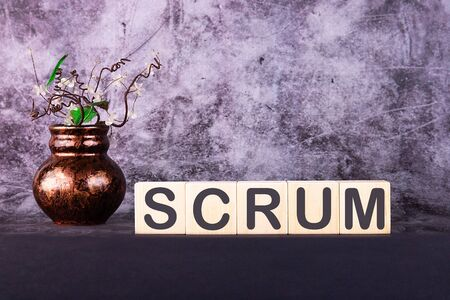 Word SCRUM made with wood building blocks on a gray back ground
