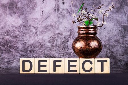 Word DEFECT made with wood building blocks on a gray back ground