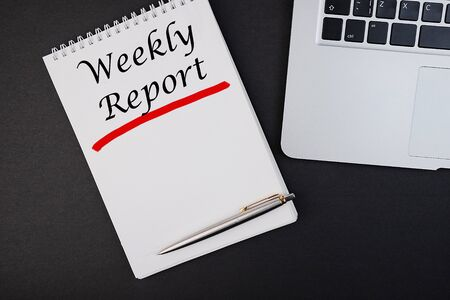 The text, the inscription, the phrase Weerly Report is written in a notebook that lies on a dark table with a laptop and pen. Business concept.