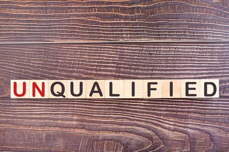 Text UNQUALIFIED is written on wooden building blocks lying on an office desk. Business concept. 版權商用圖片