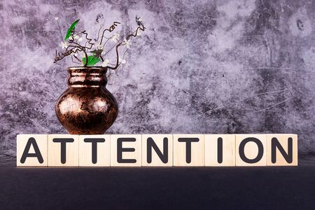ATTENTION word made with building blocks on a grey background