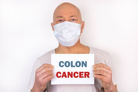 A sick man holds a tablet with the text Colon Cancer. Medical concept.