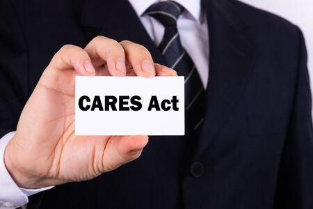 American businessman holds a card with the text CARES Act. Business concept