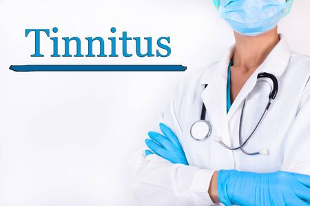 Doctor in medical clothes on a light background with the text Tinnitus. Medical concept.