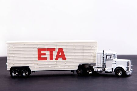 ETA word concept written on board a lorry trailer on a dark table and light background Standard-Bild