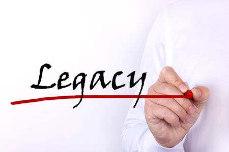 A person writes text, a word, the phrase Legacy with marker on a light background. Business concept.