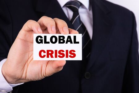A businessman is holding a tablet with the text Global Crisis in front of him in his hands. Business concept