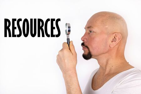 An American man looks through a magnifying glass at the word, text Resources. Business concept. Stockfoto