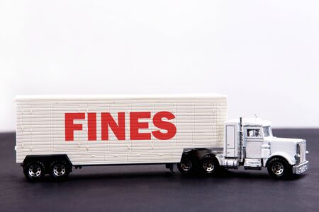 Fines word concept written on board a lorry trailer on a dark table and light background