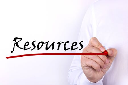A person writes text, a word, the phrase Resources with marker on a light background. Business concept. 免版税图像