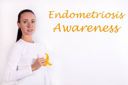 Endometriosis awareness concept. A girl in bright clothes with a yellow ribbon in her hand, as a symbol of awareness.