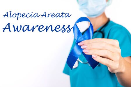 Alopecia areata awareness concept. A doctor in blue clothes with a blue ribbon in her hand, as a symbol of awarenes