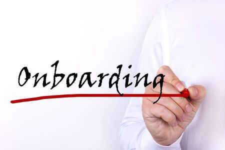 A person writes text, a word, the phrase Onboarding with marker on a light background. Business concept.