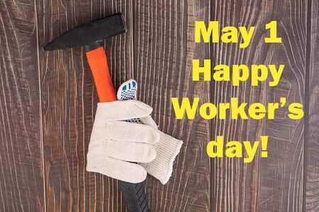 Workers' day background concept - many handy tools, notebook with happy workers' day text , wooden background, top view