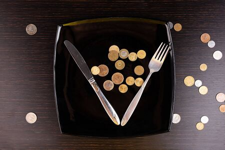 The rise in price of food, the crisis. Coins instead of food in a black plate with cutlery. Business concept.