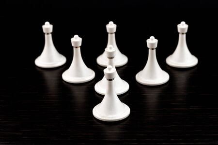White chess pieces on a chessboard on a dark background. Business concept. Game, strategy, wisdom, determination.