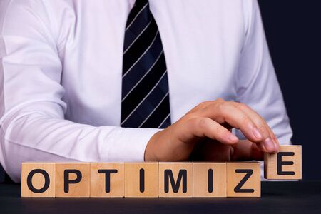 Man made word Optimize with wooden blocks. Business concept.