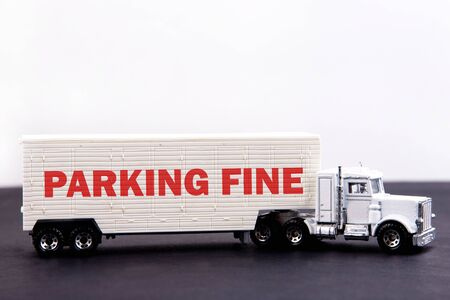 Parking fine word concept written on board a lorry trailer on a dark table and light background