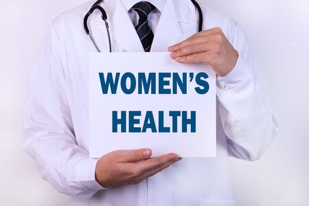 Doctor holding a card with text Women's Health , medical concept.