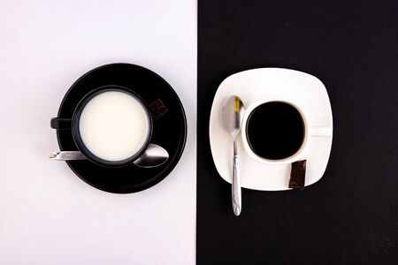 A black cup and saucer on a white background and a white cup and saucer on a black background. The concept of opposites and connections. Standard-Bild