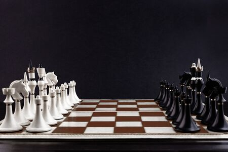 White and black chess pieces on a chessboard on a dark background. Business concept. Game, strategy, wisdom, determination. Stok Fotoğraf