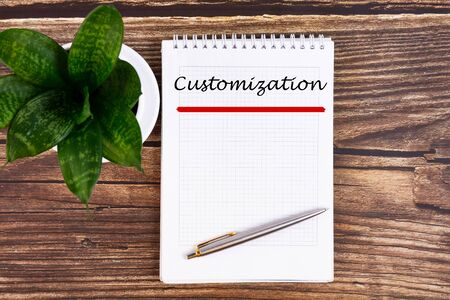 The text, the word Customization, is written in a notebook lying on a wooden table with a pen. Business concept.