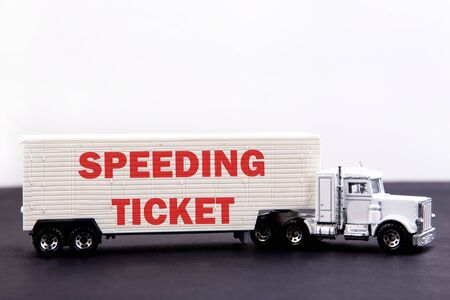 Speeding ticket word concept written on board a lorry trailer on a dark table and light background