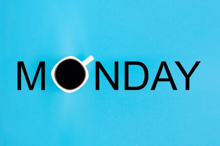 Cup of coffee as letter O in word Monday arranged from print letters on a blue background. Creative minimalist concept.