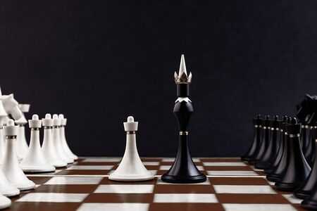 White and black chess pieces on a chessboard on a dark background. Business concept. Game, strategy, wisdom, determination. Stock Photo