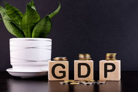 Text GDP on wood cube decorate with gold coins, economic data concept. Stock Photo