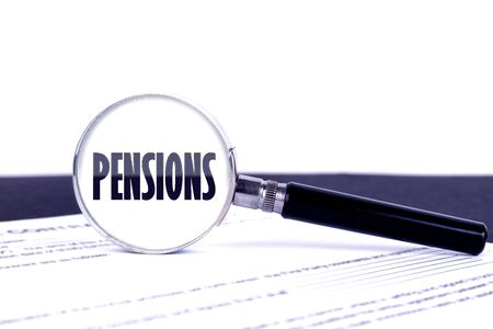 Magnifying glass with text concept word PENSIONS on a dark table and a light background.