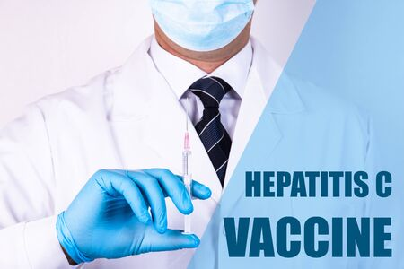Hepatitis C Vaccine text is written on the background of a doctor who is holding a syringe with a vaccine in a medical mask and gloves. Medical concept. Stock Photo