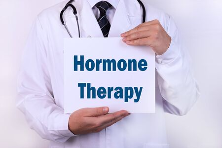 A doctor in medical clothing is holding a sign with a diagnosis in front of him, text HORMONE THERAPY Medical concept.