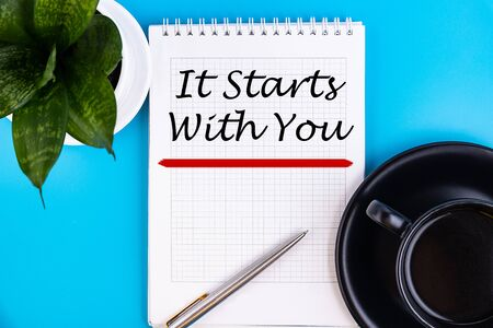 It Starts With You word concept written in notebook with a pen and a cup of coffee, top view.