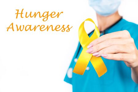 Doctor Holds Yellow Ribbon As A Sign Of Hunger Awareness